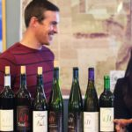 Hector Wine Company's Jason Hazlitt laughs with another staffer behind a row of wine bottles on the tasting counter