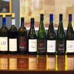 A variety of Hector Wine Company wines lined up on the wooden tasting room counter
