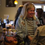 A female attendee enjoys a glass of red wine with her friend at a Hector Wine Company tasting room event