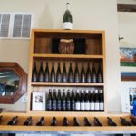 A wooden shelf holds several varieties of Hector Wine Company wines in the retail area of the winery