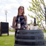 Hector Wine Company's Kirsten Emerson is ready to pour tastings outdoors by a dogwood tree, using a barrel as her table