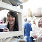 Hector Wine Company's Alex Bond pulls wine from a barrel during an event as an attendee smiles