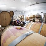 A view from the corner of Hector Wine Company's barrel room as a crowd mingles during an event