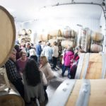 A crowd mingles during an event in the Hector Wine Company barrel room