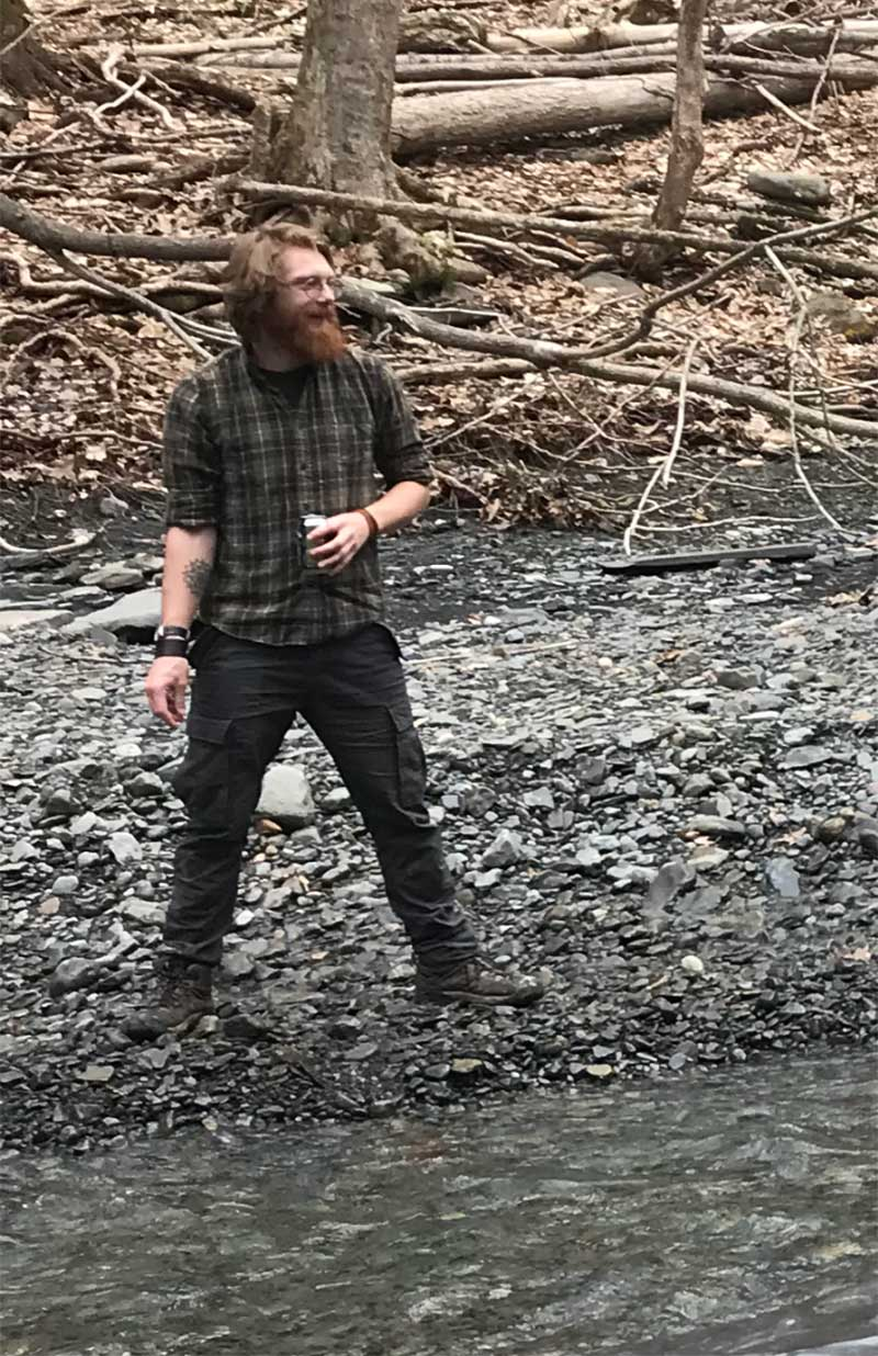 Hector Wine Company's Brandon Kendall standing on the rocky bed of a river