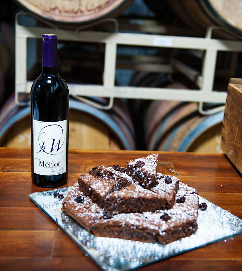 bottle of Hector Wine Company merlot red wine on a counter next to a stack of brownies