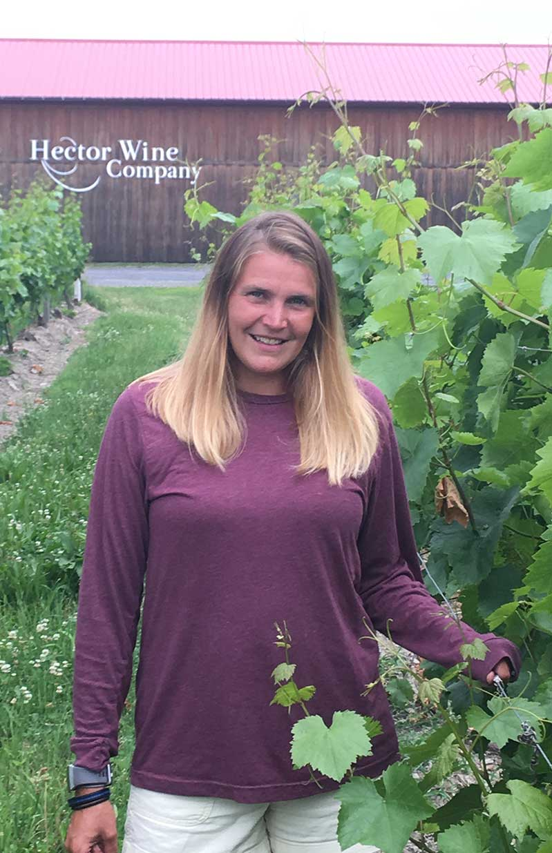 Hector Wine Company's Erin Hazlitt wearing a burgundy top in the vineyard