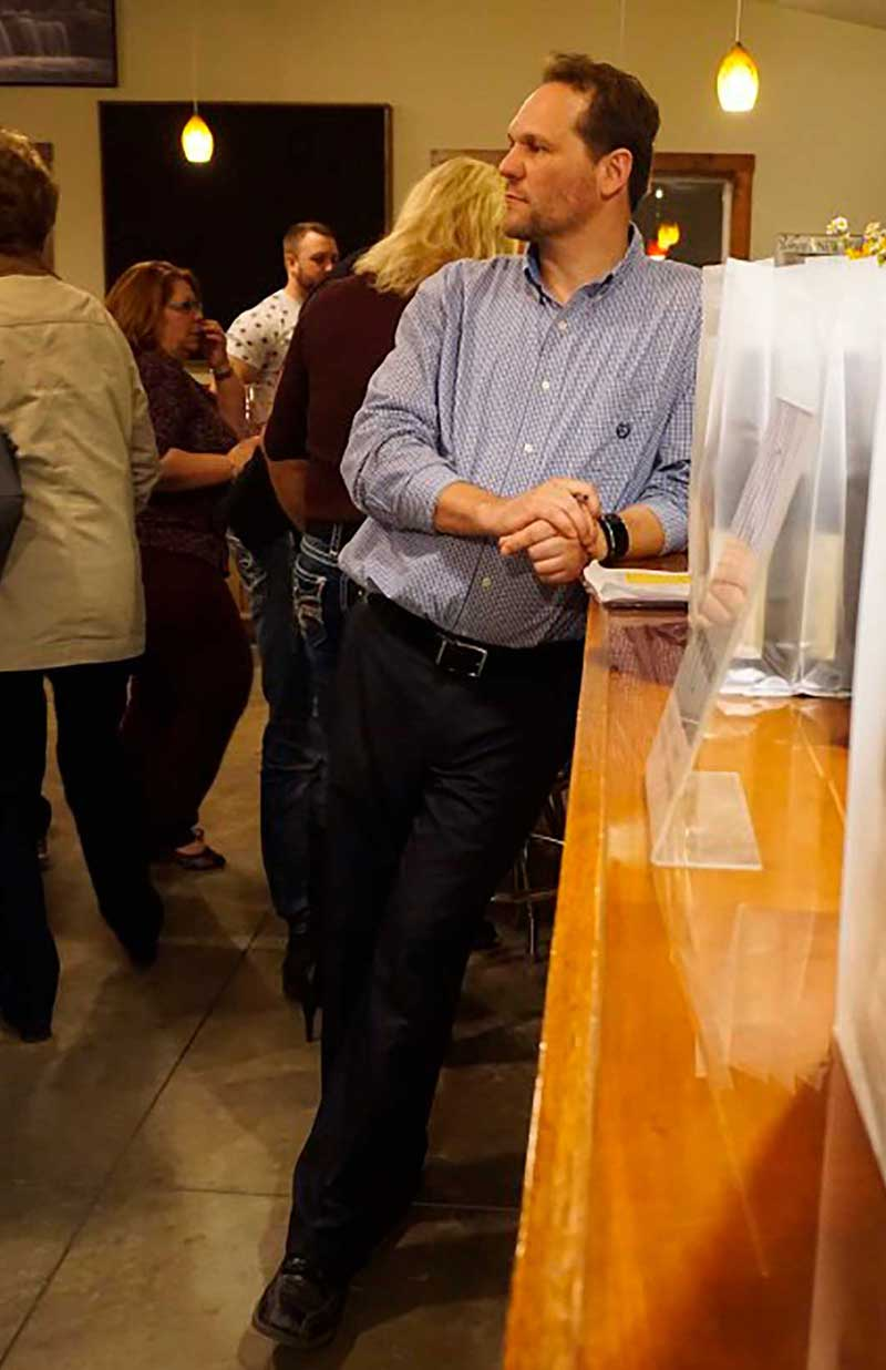 Hector Wine Company's James Heroux leaning on counter in wine tasting room