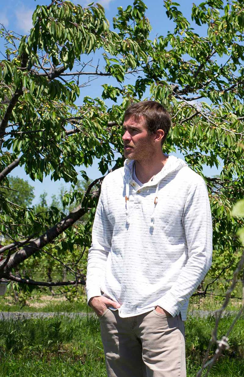 Hector Wine Company's Jason Hazlitt wearing a white hoodie and standing in front of a green leafy tree